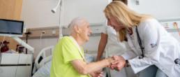 Eine Ärztin begrüsst eine ältere Patientin
