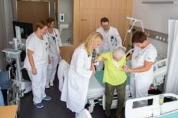 Das Behandlungsteam hilft einer älteren Patientin