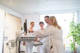 Ein Team aus Ärzten und Pflegern schaut auf einen Bildschirm