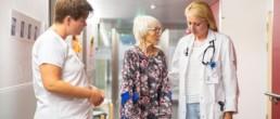 Eine ältere Patientin im Gespräch mit ihrer Ärztin und ihrer Pflegerin