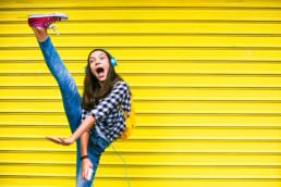 Jugendliche tanzt vor gelber Wand