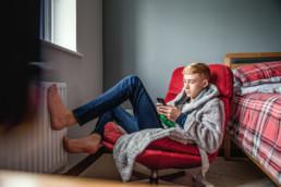 Jugendlicher sitzt in einem Sessel und schaut in sein Smartphone