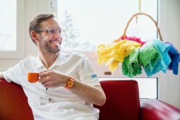 Palliativmediziner Dr. med. Manuel Jungi mit farbigen Tüchern im Hintergrund.