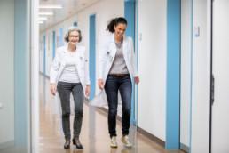 Die beiden Ärztinnen gehen den Gang entlang