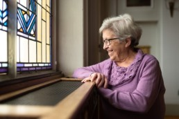 Spitalschwester Verena lächelt aus dem Fenster