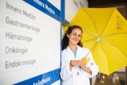 Stephanie Meyer hält einen Regenschirm in der Hand und steht vor dem Eingang des Spitals Dornach