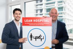 Die beiden Projektleiter Lean Management halten ein Schild