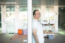 Lukas Ebnöther lehnt an einer Türe im Neubau