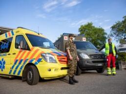 Ein Armee-Angehöriger und ein Rettungssanitäter stehen vor zwei Rettungsfahrzeugen
