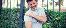 Mann hält sich die schmerzhafte Schulter