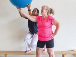 Die Physiotherapeutin und die Patientin bewegen einen Ball in die Höhe.
