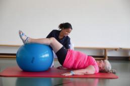 Die Patientin hebt die Beine auf einen Trainingsball.