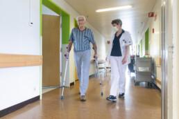 Ein älterer Patient an Krücken geht in Begleitung einer Physiotherapeutin einen Gang entlang