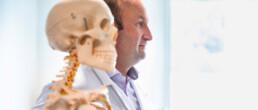 Dr. med. Michael Schmelz, Unfallchirurg, neben einem Schulungsskelett.