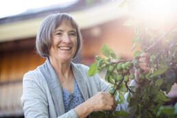 Edith Esch lachend in ihrem Garten