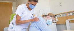 Bettina Ischi hilft einer Patientin aufzustehen.