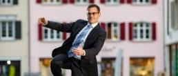 Ein Mann im Anzug springt von einem Bank