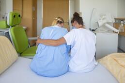 Eine Kinästhetik-Trainerin sitzt neben einer Patientin auf dem Bett