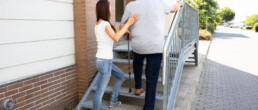 Eine Frau unterstützt einen Mann beim Treppensteigen