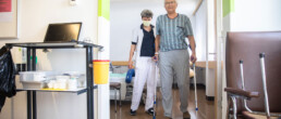Ein Patient geht einen Gang entlang, unterstützt von einer Therapeutin