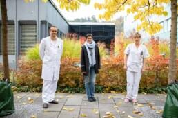 Chefarzt, Patientin und Pflegefachfrau stehen nebeneinander