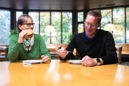 Eine Frau isst einen Hamburger, neben ihr ein Mann ein Salat