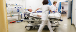 Zwei Pflegerinnen schieben einen Patienten im Bett