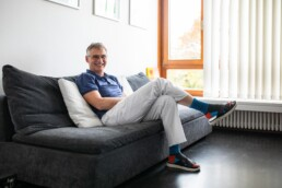 Andreas Gösele sitzt auf einem Sofa